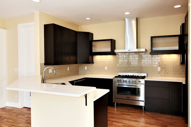 dark cabinets, white quartz countertop with stainless steel appliances